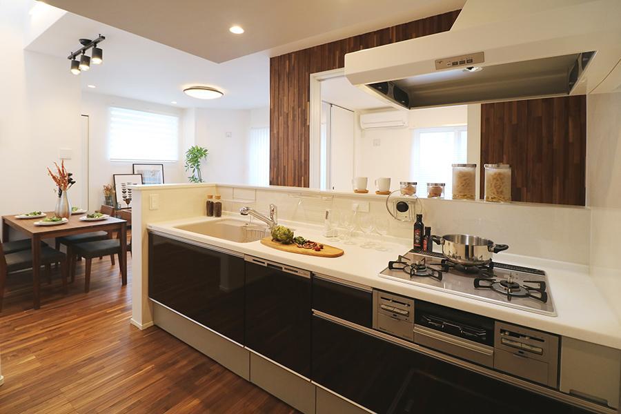 【モデルハウス_ワイドオープンキッチン】<BR>天井をアクセントクロスでくるんだ高級感あるオープンンキッチン。キッチン側カウンター前には少し高さを設けてあるので、見せたくない手元は隠せます。