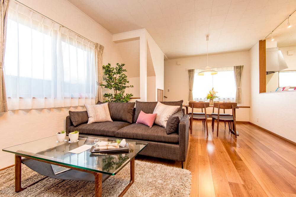 【8号地モデルハウス・リビング】<BR>自然光で明るく風通しのいいリビング。フローリングは、ブラウンカラーを採用し、木のぬくもりを感じる空間に。カウンターキッチンを採用し、ご家族での会話も弾みます。