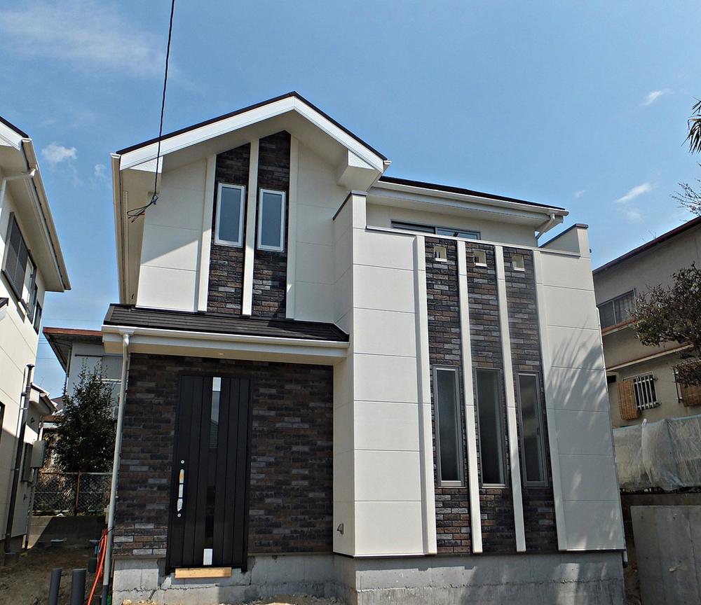 現地外観。 外壁は、防音・撥水・高耐久・軽量・高断熱のコンクリートボードにアクセントタイルで高級感を演出