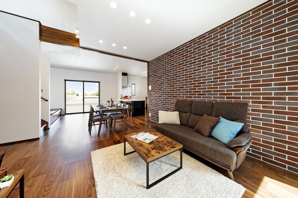 リビングの壁面の一部に、空間のアクセントとなるレンガ風の壁紙をチョイス。リビング階段や吹抜けを採用し、家族のコミュニケーションを育めるプランニングです(8号地モデルハウス)