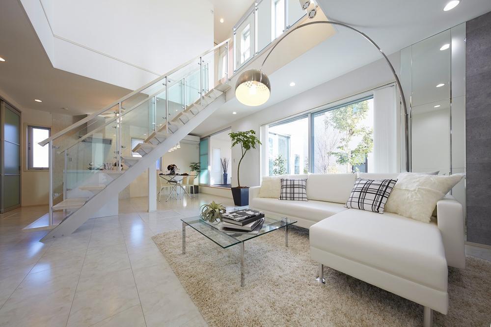 白を基調とした明るいリビングの中心には大胆な階段を。デザイン性を追求しつつ、透明パネルが落下防止にもなり、小さなお子様がいるご家庭でも心配なく生活していただけます。/当社施工例