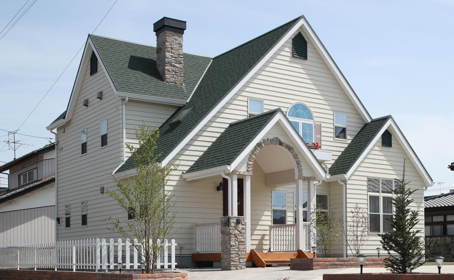 暮らしを彩る大好きなデザイン。青空と花が似合う三角屋根のラップサイディングの家画像1