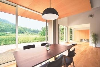 リビング・ダイニングは天井に木を張り、壁にはチークのウッドタイルを使って木質感の豊かな空間に仕上げている。吹抜けは2階のホールとつながる設計